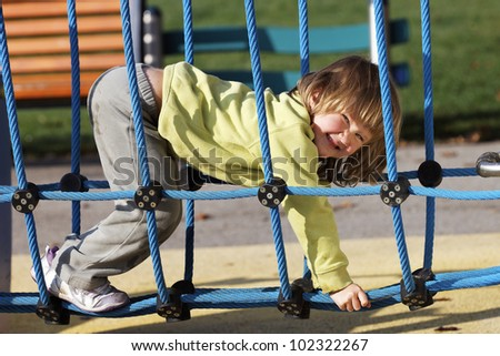 joyful child playing on colorful playground in a park - stock photo