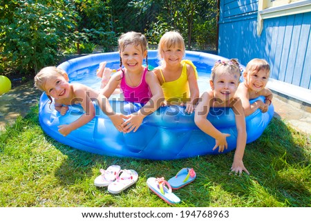Joyful Children playing in inflatable pool - stock photo