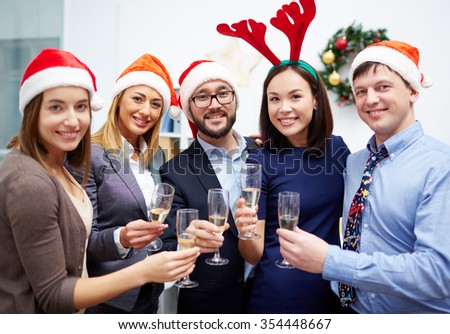 Joyful colleagues with flutes of champagne looking at camera at Christmas party - stock photo