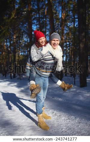 Joyful couple in knitted winterwear having fun in winter forest - stock photo