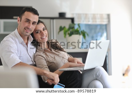 joyful couple relax and work on laptop computer at modern living room indoor home - stock photo