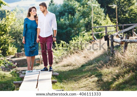 Joyful couple standing together, outdoor, countryside. Girl wearing blue dress and light blue shoes and man wearing white shirt and claret trousers. Full body - stock photo