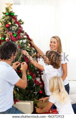 Joyful family decorating Christmas tree at home - stock photo