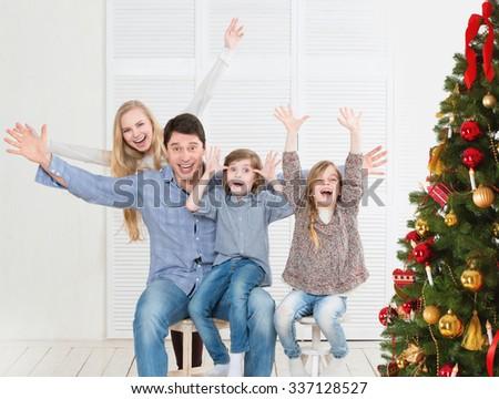 Joyful family home near the Christmas tree. New Year's and Christmas. - stock photo