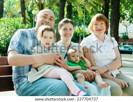 joyful family of five with grandmother enjoying time at city street in summer  - stock photo