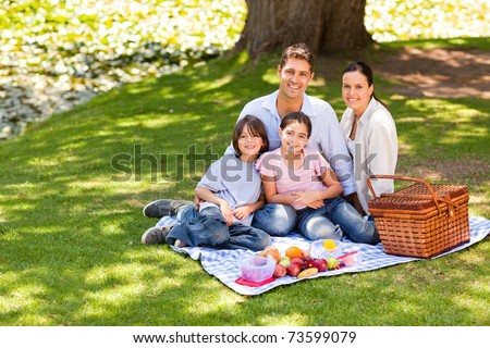 Joyful family picnicking in the park - stock photo