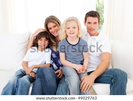 Joyful family watching television sitting on sofa at home - stock photo