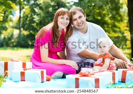 Joyful family with colorful gift boxes playing - stock photo