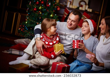Joyful family with xmas gifts staying at home on holiday eve - stock photo
