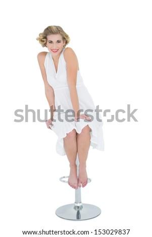 Joyful fashion blonde model sitting on bar chair on white background - stock photo