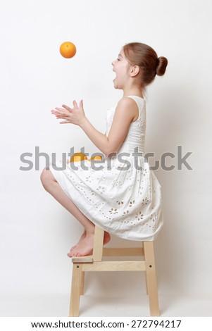 Joyful fashion little girl holding organic oranges - stock photo
