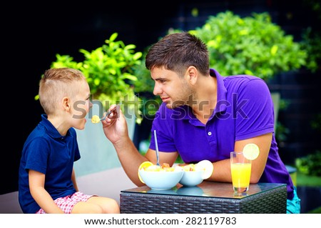 joyful father feeding son with tasty fruit salad - stock photo