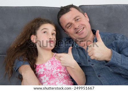 Joyful father with daughter showing thumbs up. Fathers day - stock photo
