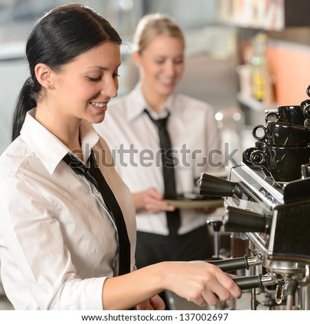 Joyful female barista operating coffee maker machine in coffee shop - stock photo