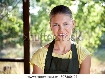 Joyful female small business owner wearing apron standing outside the market. Young woman gardener selling homegrown fruits and vegetables.  - stock photo