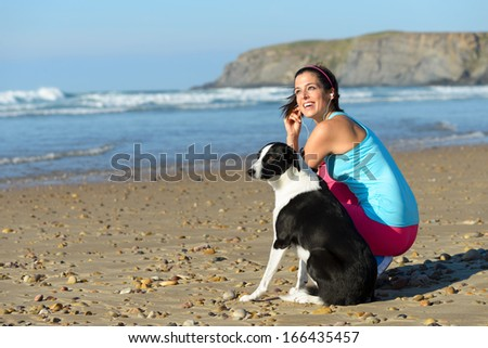 Joyful fitness woman with dog on beach taking a break from running. Sporty girl with her pet on summer sport  and relaxing day. - stock photo