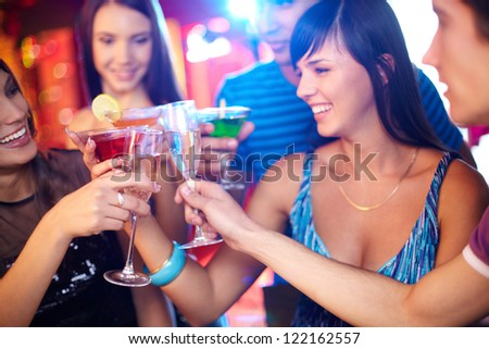 Joyful friends toasting at birthday party with focus on champagne flutes - stock photo
