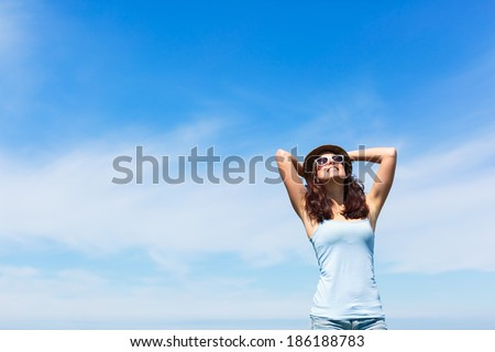 Joyful funky woman on copy space sky background. Brunette girl enjoying freedom and leisure on summer or spring. - stock photo