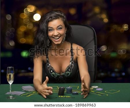 Joyful girl in casino win in poker - stock photo