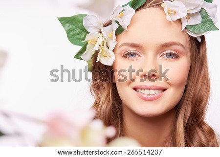 Joyful girl in floral wreath looking at camera with toothy smile - stock photo