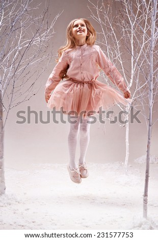 Joyful girl in pink dress jumping in magic forest among bare trees - stock photo