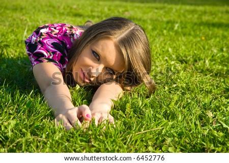 Joyful girl on a green grass. - stock photo