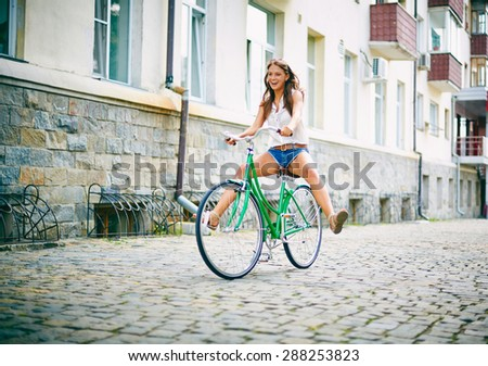 Joyful girl on bicycle having fun - stock photo