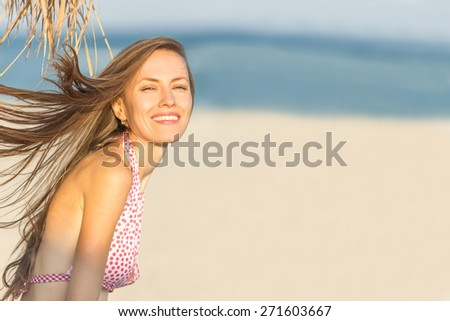 Joyful girl  playing and having fun in sunny tropical destination for travel holiday. shallow DOF, focus on woman's eyes and lips - stock photo