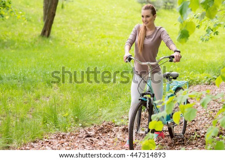 Joyful girl traveling with bike in forest - stock photo