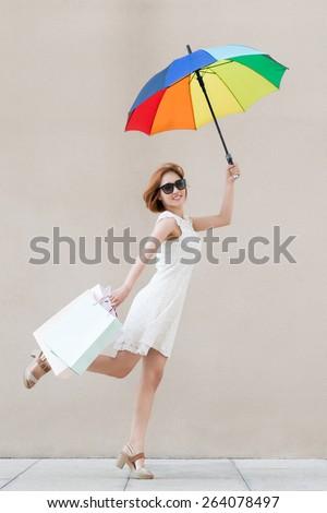 Joyful girl with colorful umbrella and shopping bags - stock photo