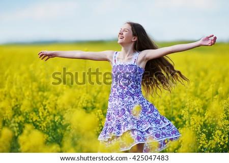 joyful girl with flower garland at yellow rape seed meadow - stock photo