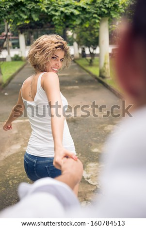 Joyful girlfriend leading her boyfriend by the hand in the park on the foreground - stock photo