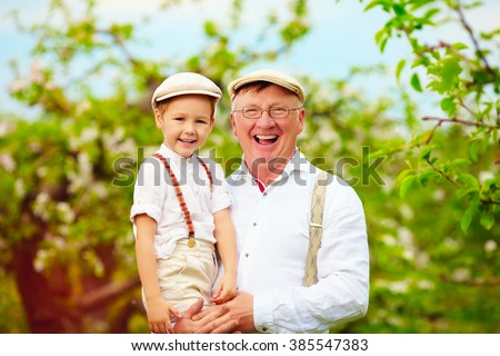 joyful grandpa and grandson having fun in spring apple garden - stock photo