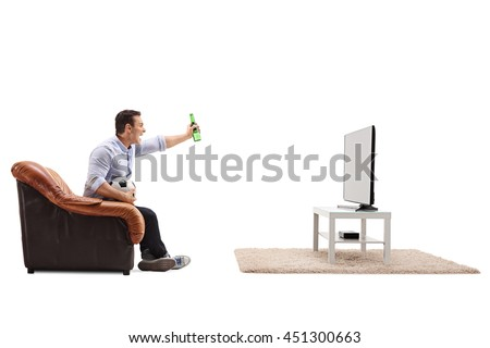 Joyful guy watching football on TV and celebrating with a beer isolated on white background - stock photo