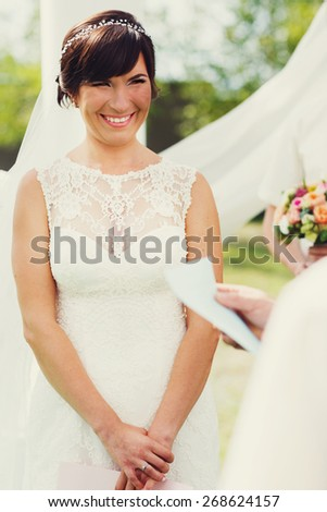 joyful happy smiling bride in a white dress with lace at a wedding ceremony - stock photo