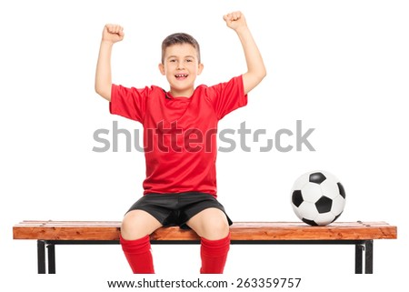 Joyful junior soccer player in red shirt gesturing happiness seated on wooden bench isolated on white background - stock photo