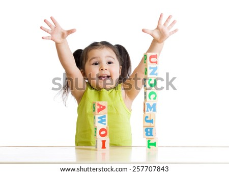 joyful kid girl plays with cubes isolated - stock photo