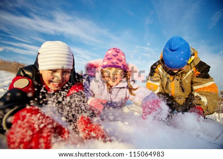 Joyful kids in winterwear having happy time outside - stock photo