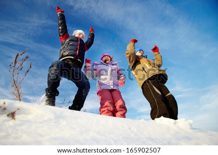 Joyful kids in winterwear having happy time outside in winter - stock photo