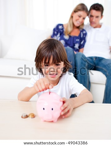 Joyful little boy inserting coin in a piggybank in the living room - stock photo