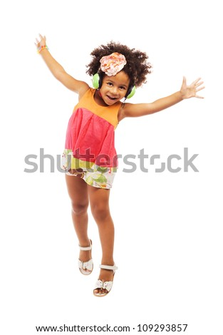 Joyful little girl in headphones is jumping - stock photo