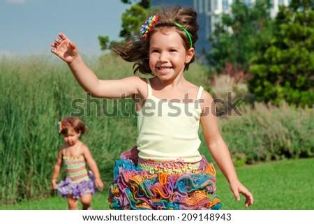 Joyful little girl running on the grass in the summer - stock photo