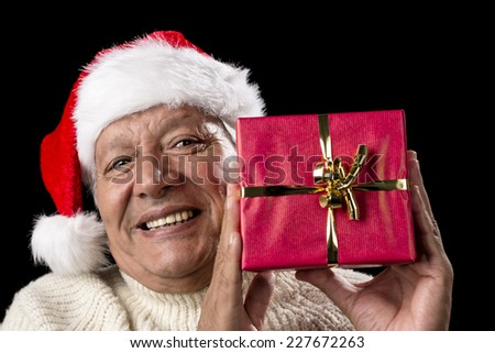 Joyful male senior is presenting a red wrapped Christmas present. He is wearing a Santa Claus hat and a warm white pullover. Isolated on black background. Gift-giving theme for December. - stock photo