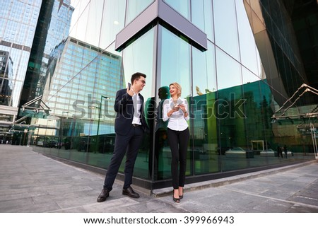 Joyful man and woman bosses dressed in corporate clothes with cellphones in hands are discussing their successful signing contract with clients, while are standing outdoors against skyscraper building - stock photo