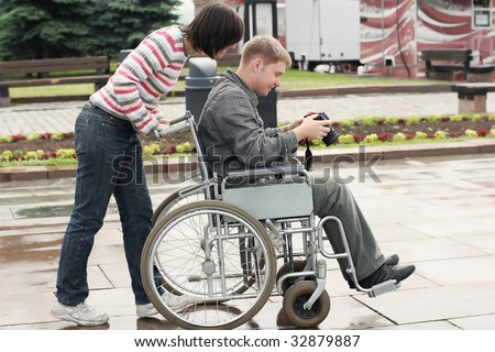 Joyful man on a wheelchair looking image in the camera - stock photo