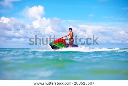 joyful man riding jet ski, tropical ocean - stock photo