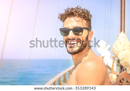 Joyful man take self portrait on exclusive luxury sailing boat. Concept of friendship and travel with young people. Happy guy spending time with friends during summer trip with bright sunny color tone - stock photo