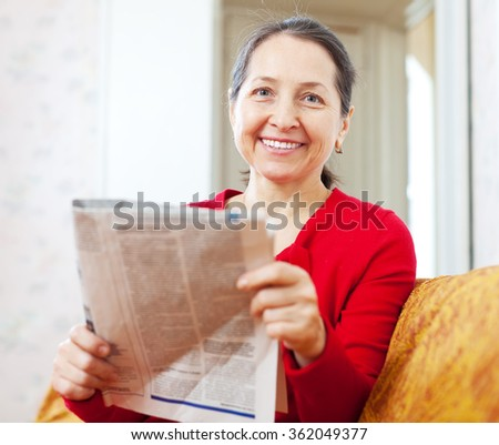 Joyful mature woman sits on sofa with newspaper  - stock photo