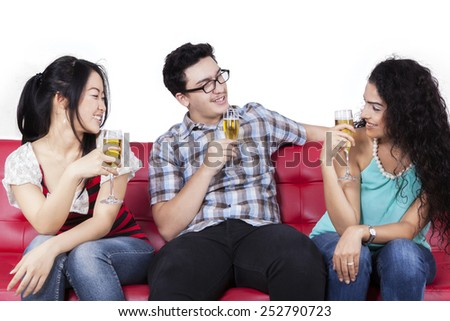 Joyful multi ethnic people sitting on couch while drinking beer together, isolated on white background - stock photo