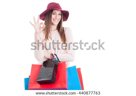 Joyful pretty female wearing casual dress and hat showing ok sign and carrying shopping bags isolated on white with advertising area - stock photo